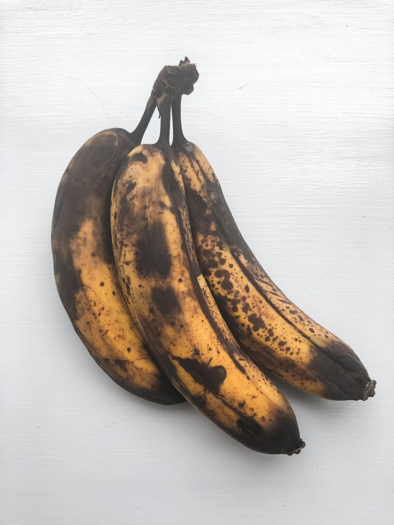 bunch of ripe bananas on a white surface