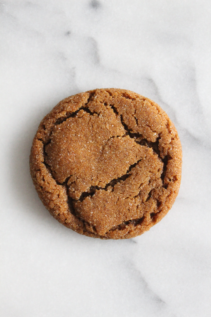 close-up overhead view of a chewy molasses cookie on a marble surface