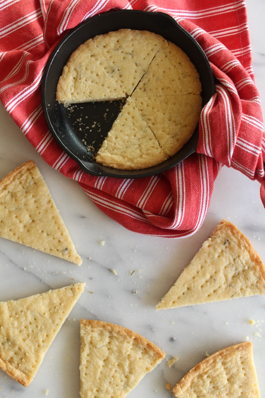 overhead view of shortbread in a cast iron skillet on a marble surface with a red kitchen towel