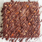 overhead view of chocolate fudge topped with chopped chocolate candy and a drizzle of melted chocolate
