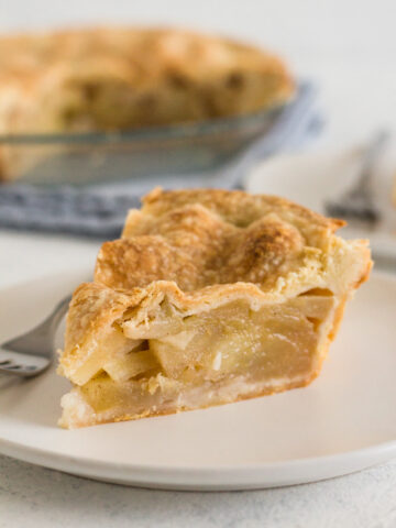 close-up side view of a slice of apple pie on a white plate with a fork and with the rest of the pie in the background