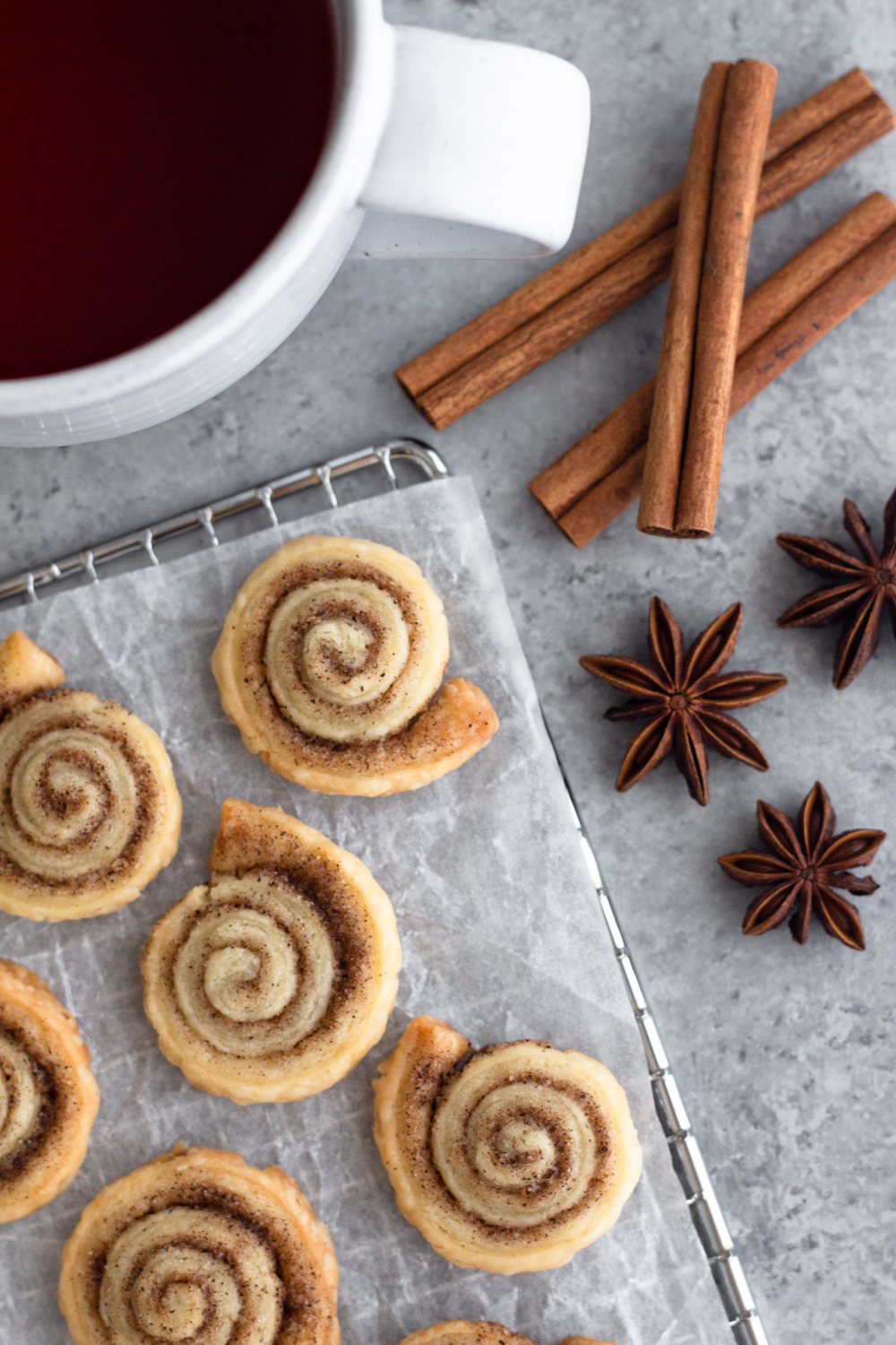 overhead view of pie crust cookies on a cooling rack with cinnamon sticks, star anise, and a mug of tea