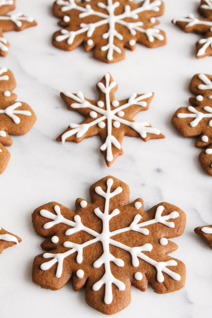 angled view of snowflake gingerbread cookies with icing on a marble surface