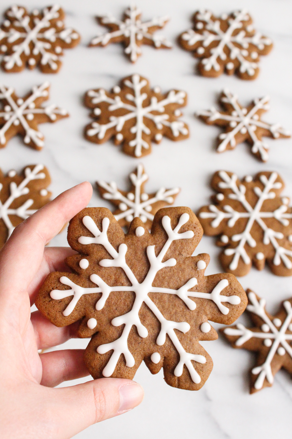 hand holding a snowflake gingerbread cookie with icing over a marble surface