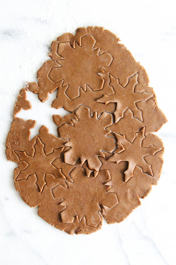 overhead view of gingerbread cookie dough with snowflake cutouts on a marble surface