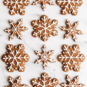 overhead view of snowflake gingerbread cookies with icing on a marble surface