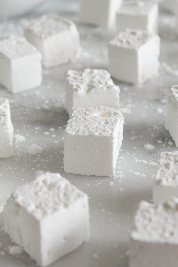 side view of homemade marshmallows scattered on a marble surface