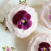 overhead view of cupcakes with pink frosting and purple flower garnish