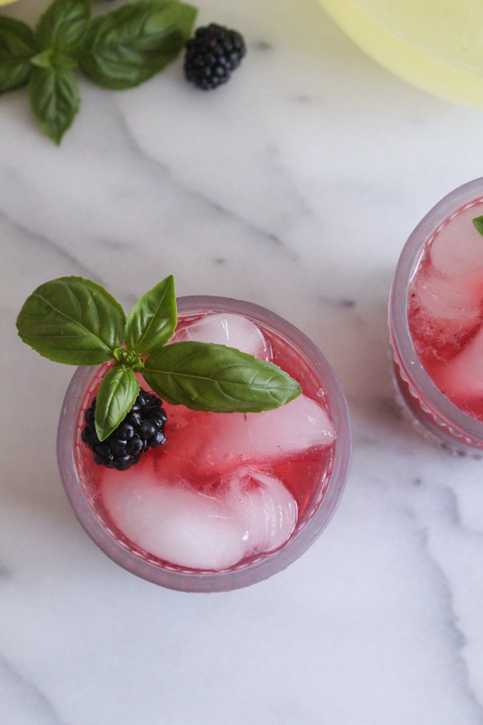 overhead view of blackberry lemonade in a glass garnished with a fresh basil sprig
