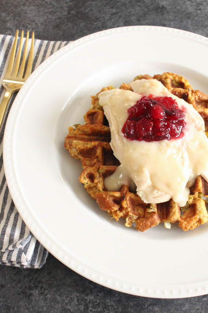 waffle on a plate topped with turkey and cranberry sauce