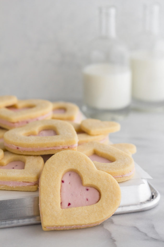 angled view of Valentine heart sugar cookies with pink raspberry buttercream frosting stacked on a baking sheet on top of a marble surface