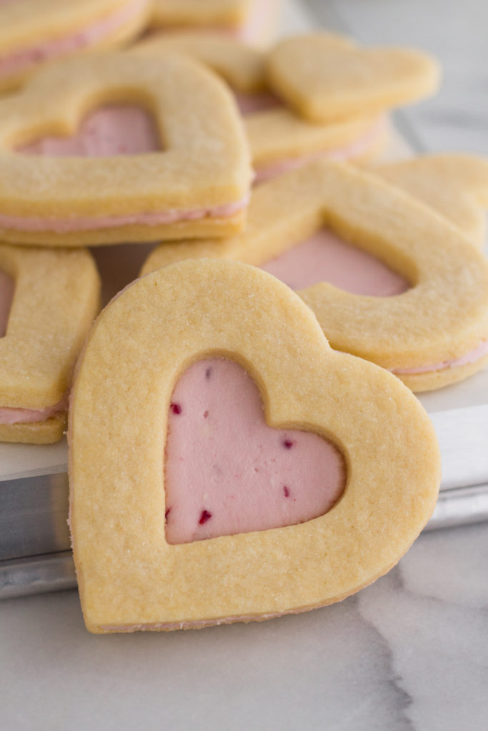 close up view of Valentine heart sugar cookies with pink raspberry buttercream frosting stacked on a baking sheet