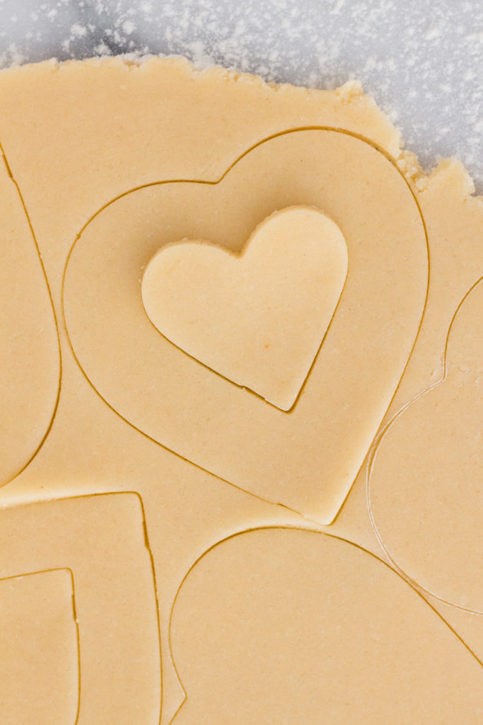 overhead view of sugar cookie dough rolled out on a marble surface with heart-shaped cutouts