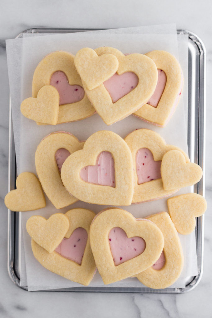 overhead view of Valentine heart sugar cookies with pink raspberry buttercream frosting stacked on a baking sheet