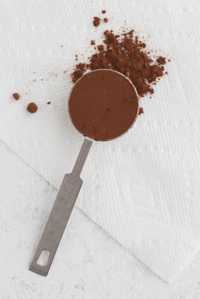 cocoa powder in a measuring spoon on a white surface