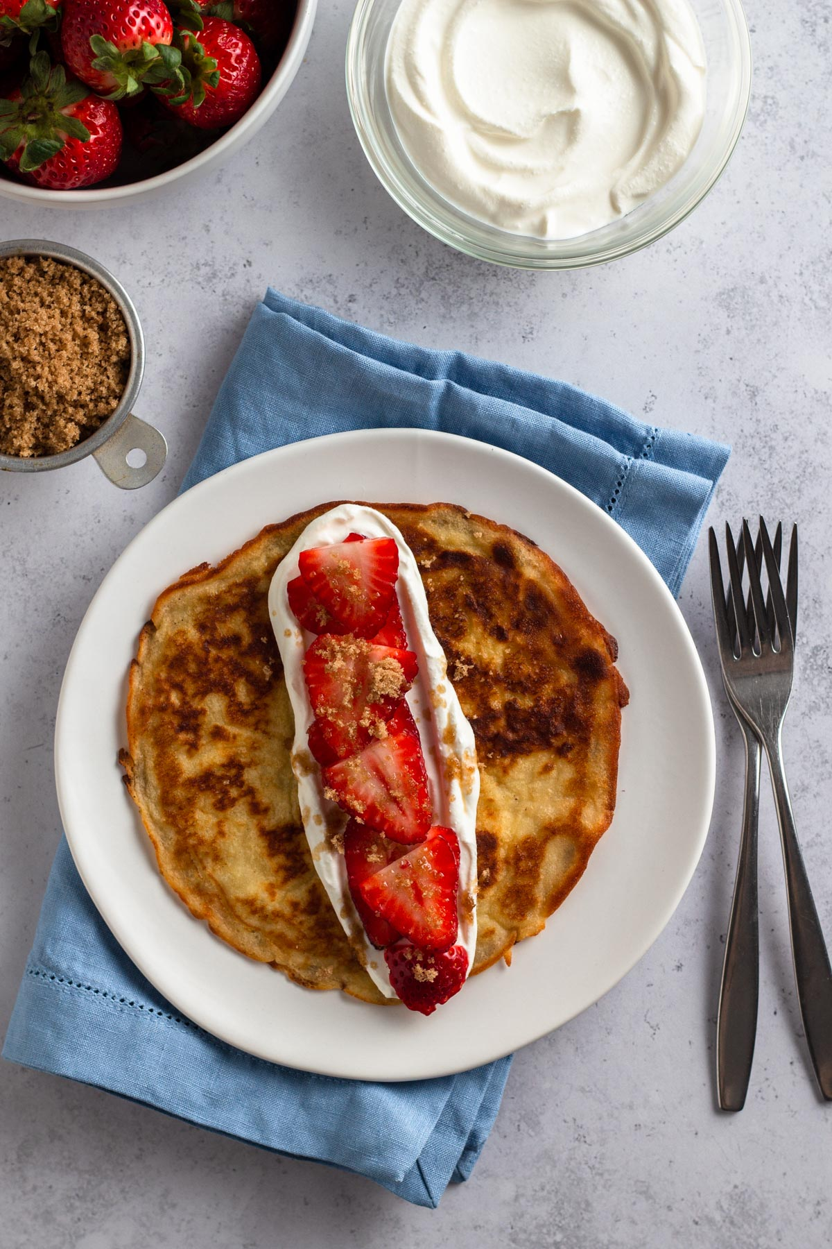 overhead view of crepe pancakes on a white plate topped with brown sugar, sour cream, and fresh strawberries