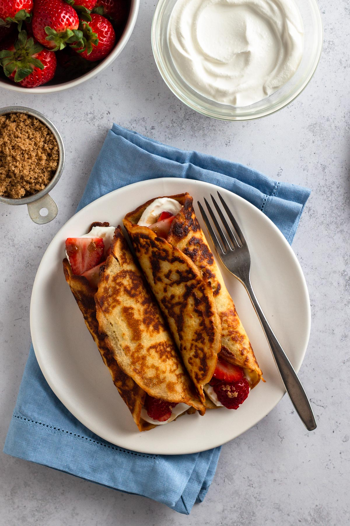 overhead view of rolled up crepe pancakes on a white plate with a blue napkin, brown sugar, sour cream, and fresh strawberries