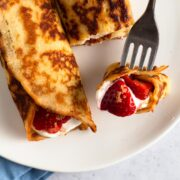 close up view of rolled crepe pancakes with fresh strawberries on a white plate
