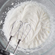 homemade whipped cream in a glass bowl with handheld electric mixer on a gray surface
