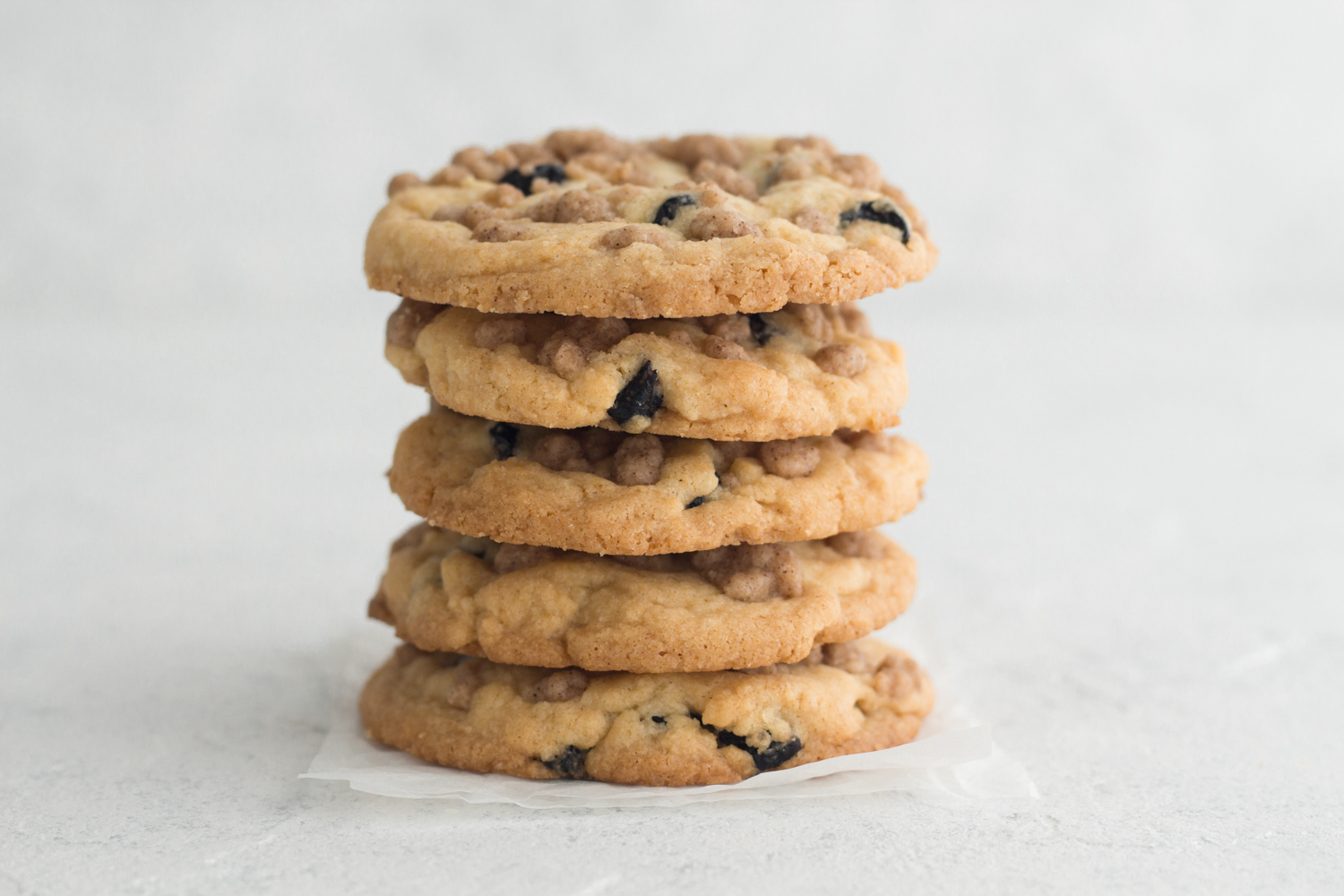 side view of blueberry cookies with streusel topping stacked on a white background