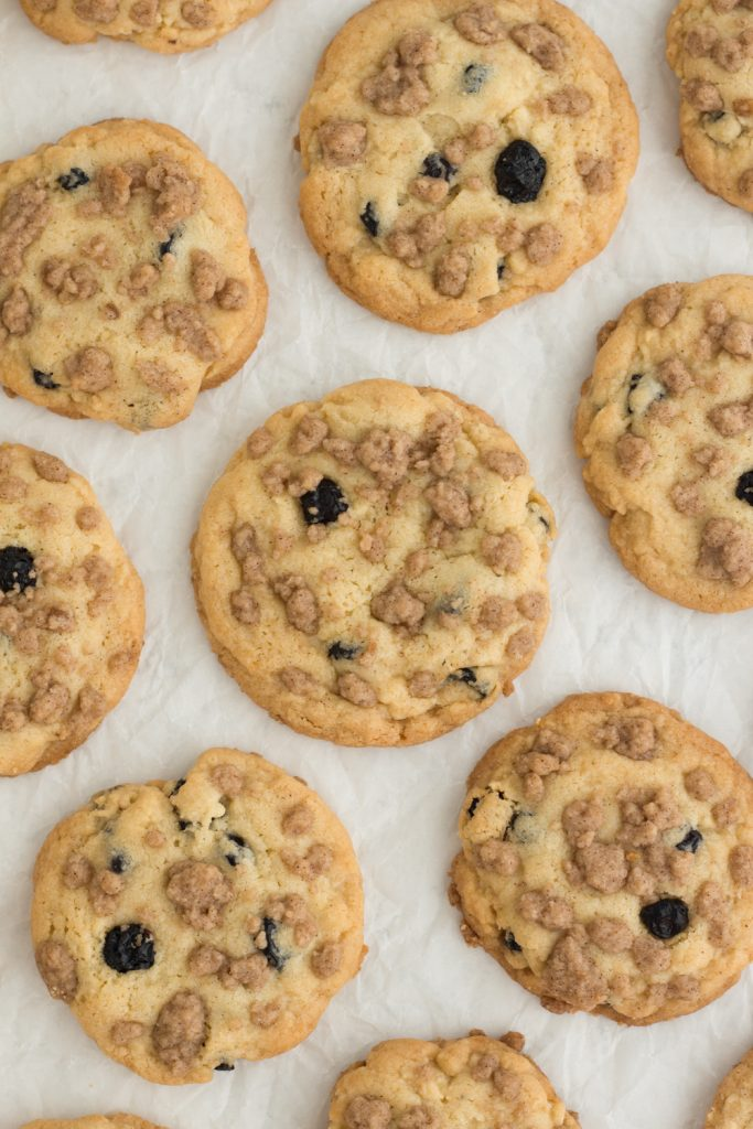 overhead view of blueberries cookies with streusel topping on a white background