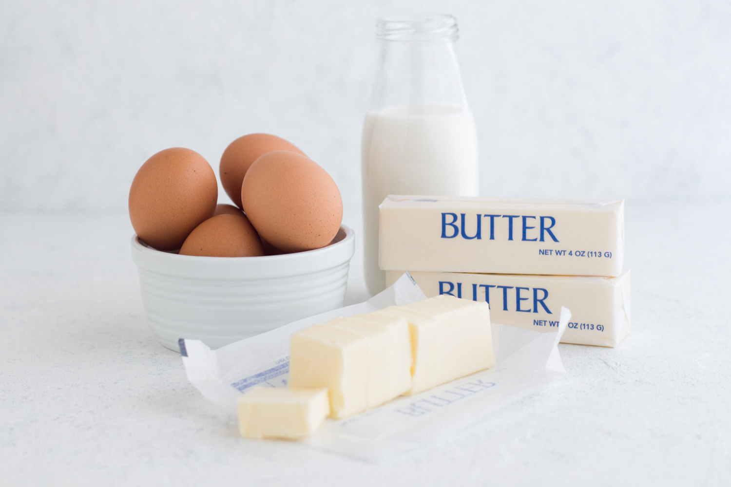 butter, brown eggs, and a glass of milk on a white surface