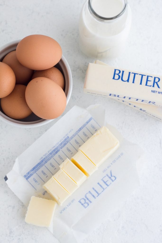 overhead view of sliced butter, brown eggs, and a glass of milk on a white surface