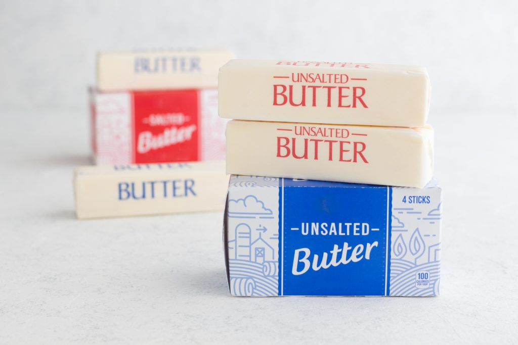 sticks of butter and butter boxes stacked on a white surface