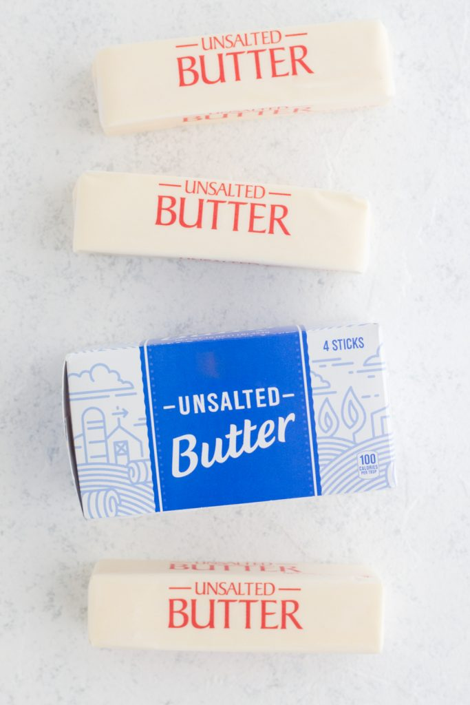overhead view of unsalted butter sticks and butter box laying on a white surface