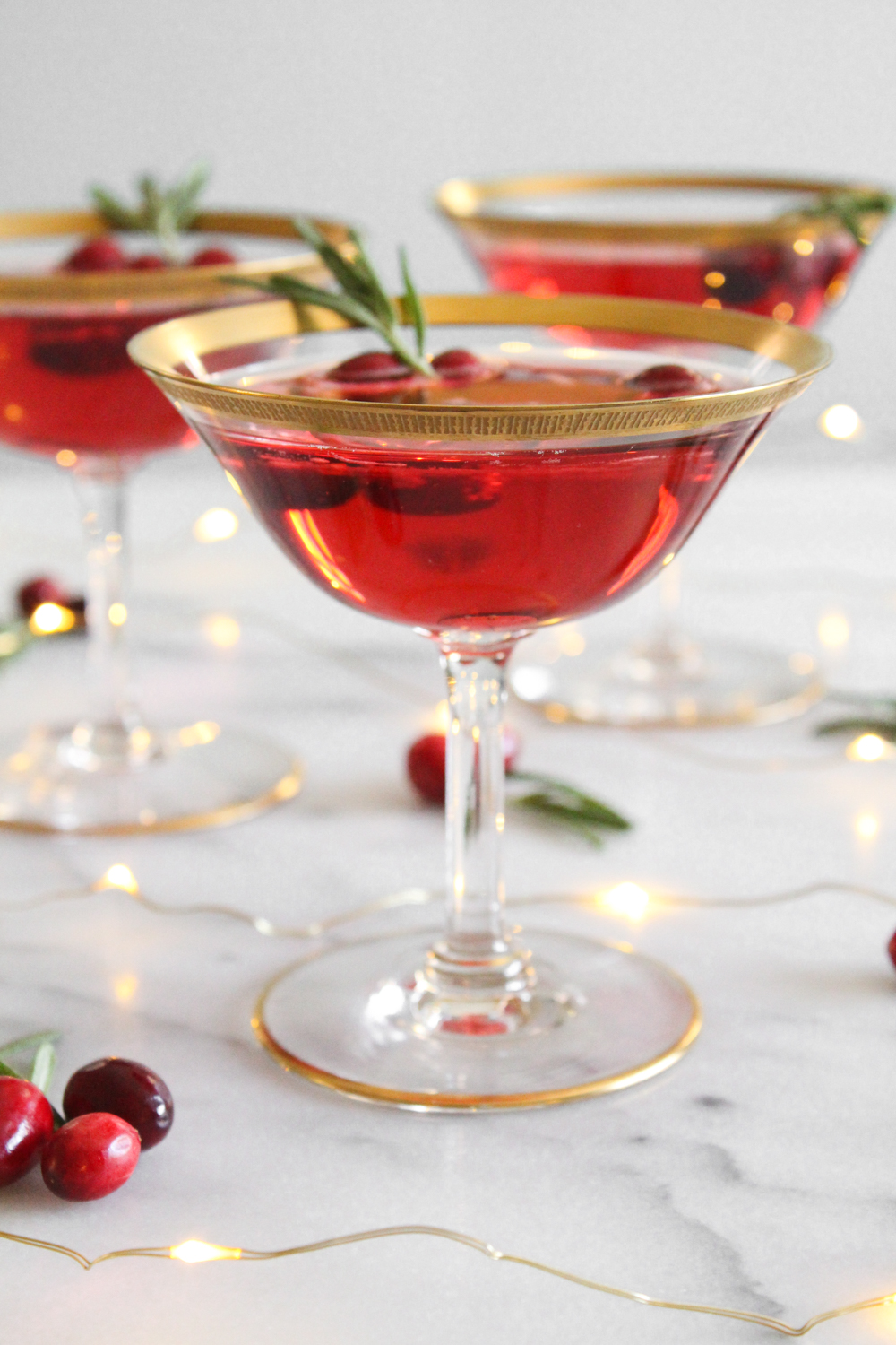 side view of 3 cranberry champagne cocktail in gold-rimmed coupe glasses on a marble surface