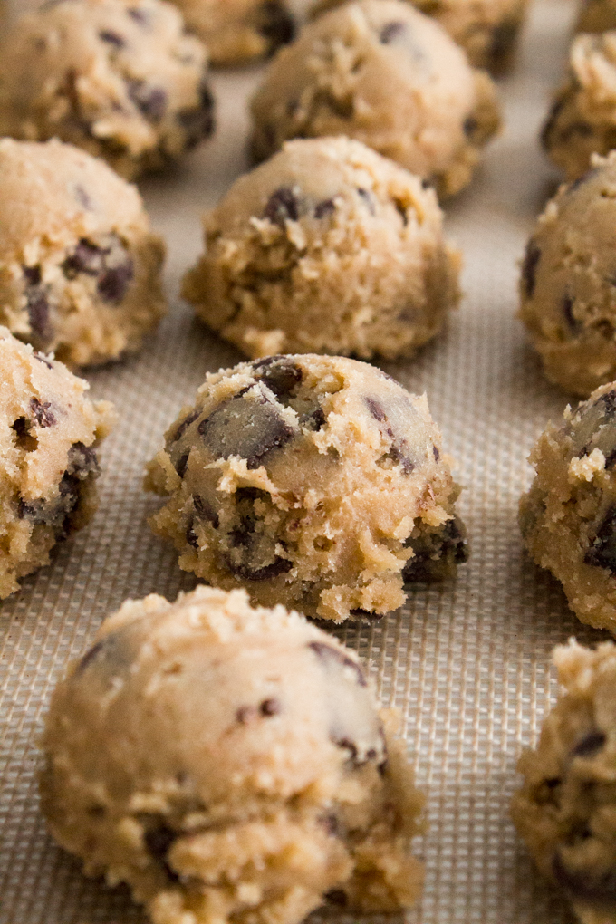 angled view of raw cookie dough scooped into balls on a silicone baking mat