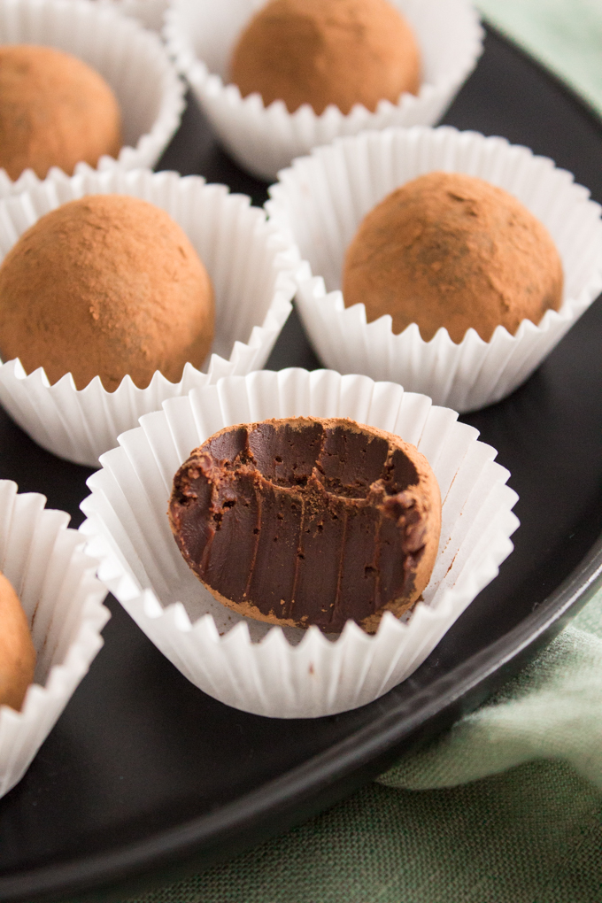 angled side view of Irish cream chocolate truffles with a bite missing on a black plate on top of a green linen napkin