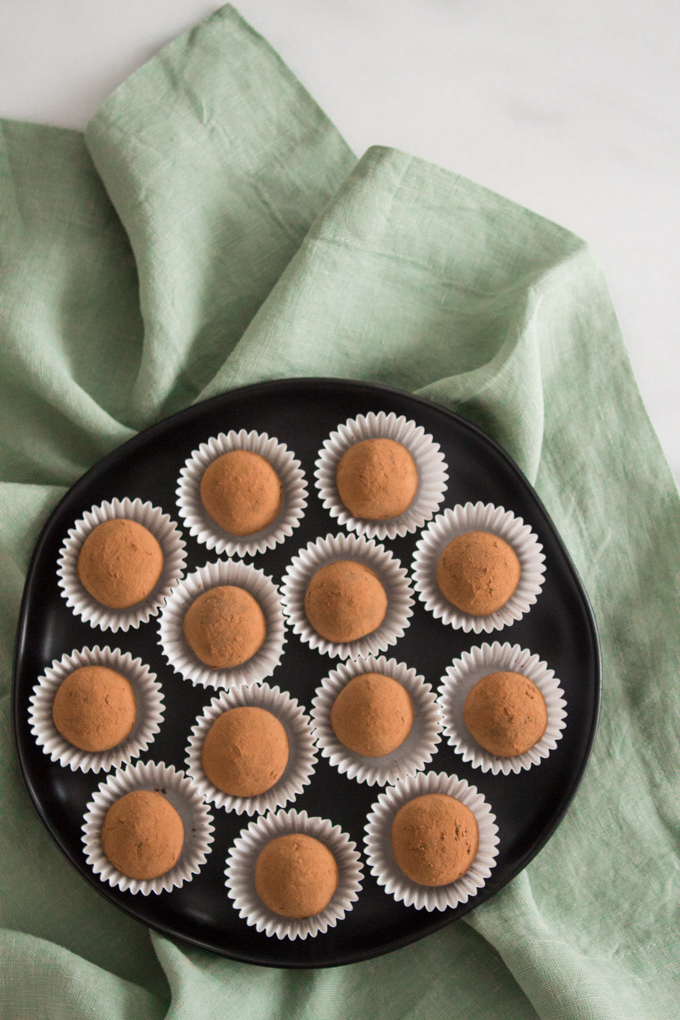 overhead view of Irish cream chocolate truffles on a black plate on top of a green linen napkin