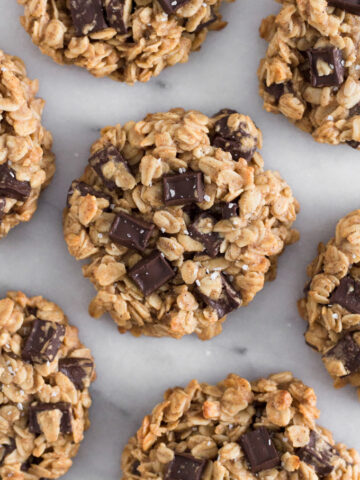 overhead view of oatmeal dark chocolate chunk breakfast cookies scattered on a marble surface