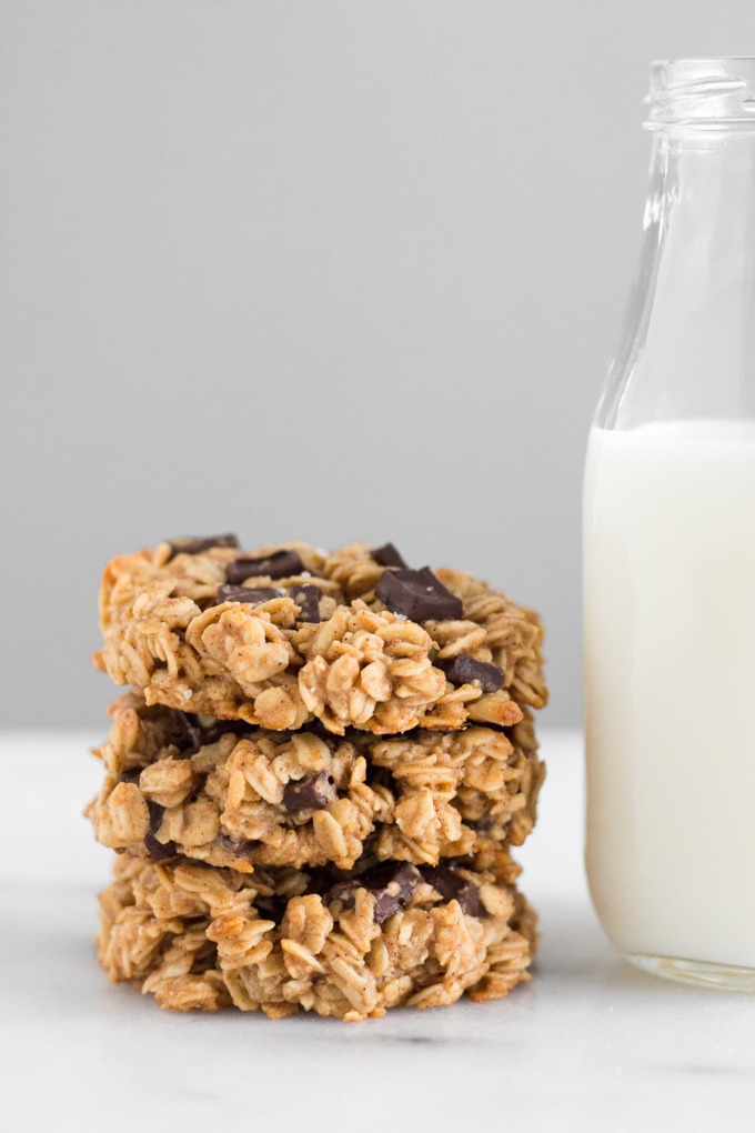 stacked oatmeal dark chocolate chunk breakfast cookies with a glass of milk on a marble surface