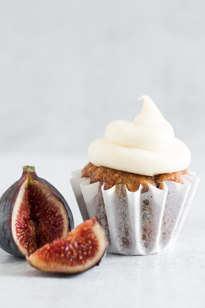 fig cupcake with swirled honey cream cheese frosting and a sliced fig