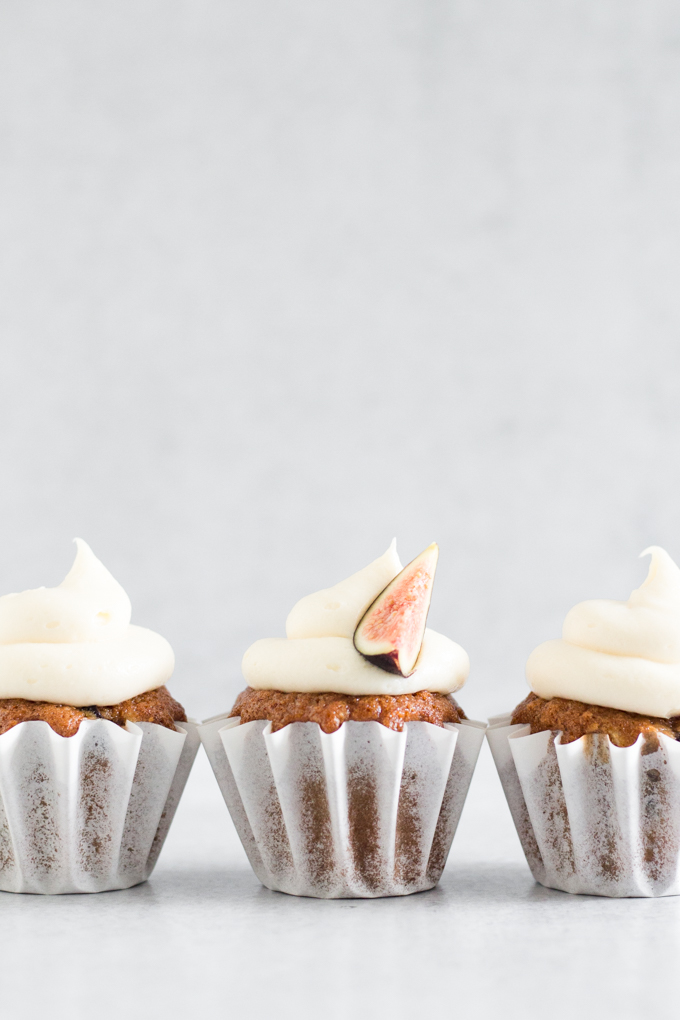 side view of fig cupcakes with swirled honey cream cheese frosting in a line