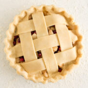 overhead view of an unbaked pie with lattice top on a white surface