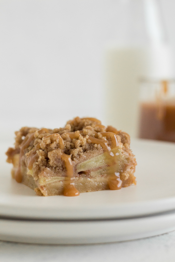 side view of an apple pie bar on a white plate with a pot of salted caramel sauce and a glass of milk