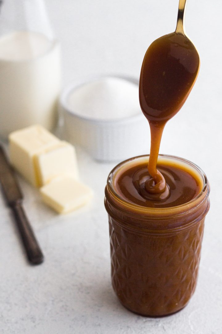 angled view of homemade salted caramel sauce being drizzled from a gold spoon into a glass jar on a white surface with sugar, butter, and cream in the background