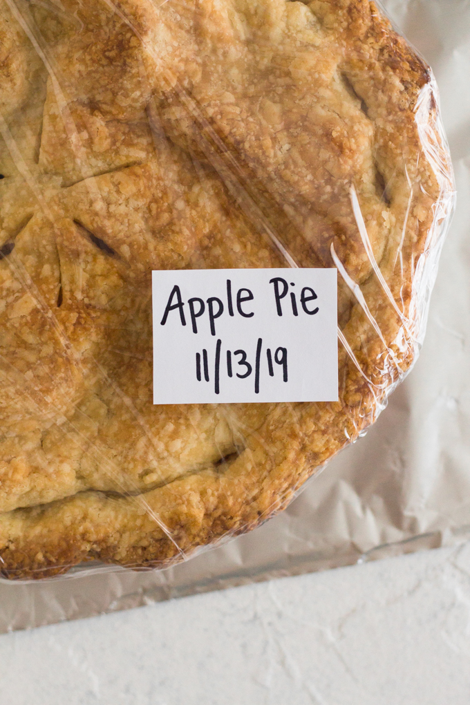 baked apple pie wrapped in plastic with aluminum foil on a white surface