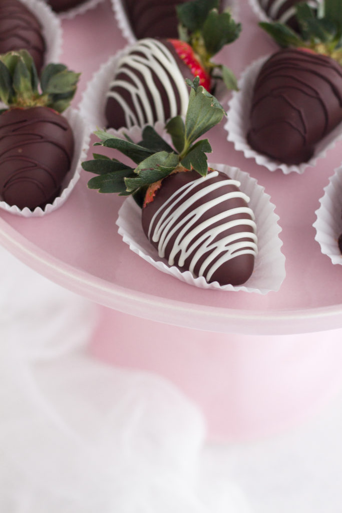 overhead view of chocolate covered strawberries with white chocolate drizzle on a pink cake stand