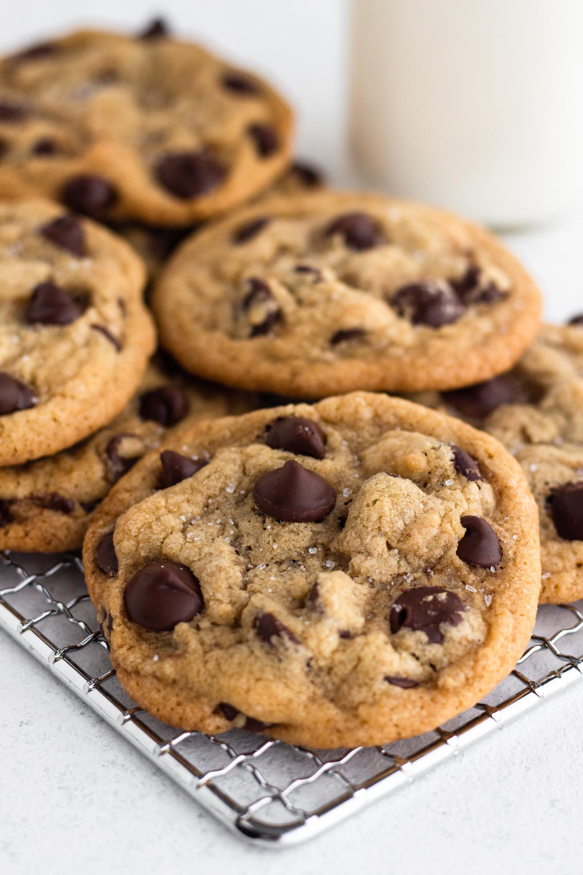 no chill chocolate chip cookies on a cooling rack next to a glass of milk