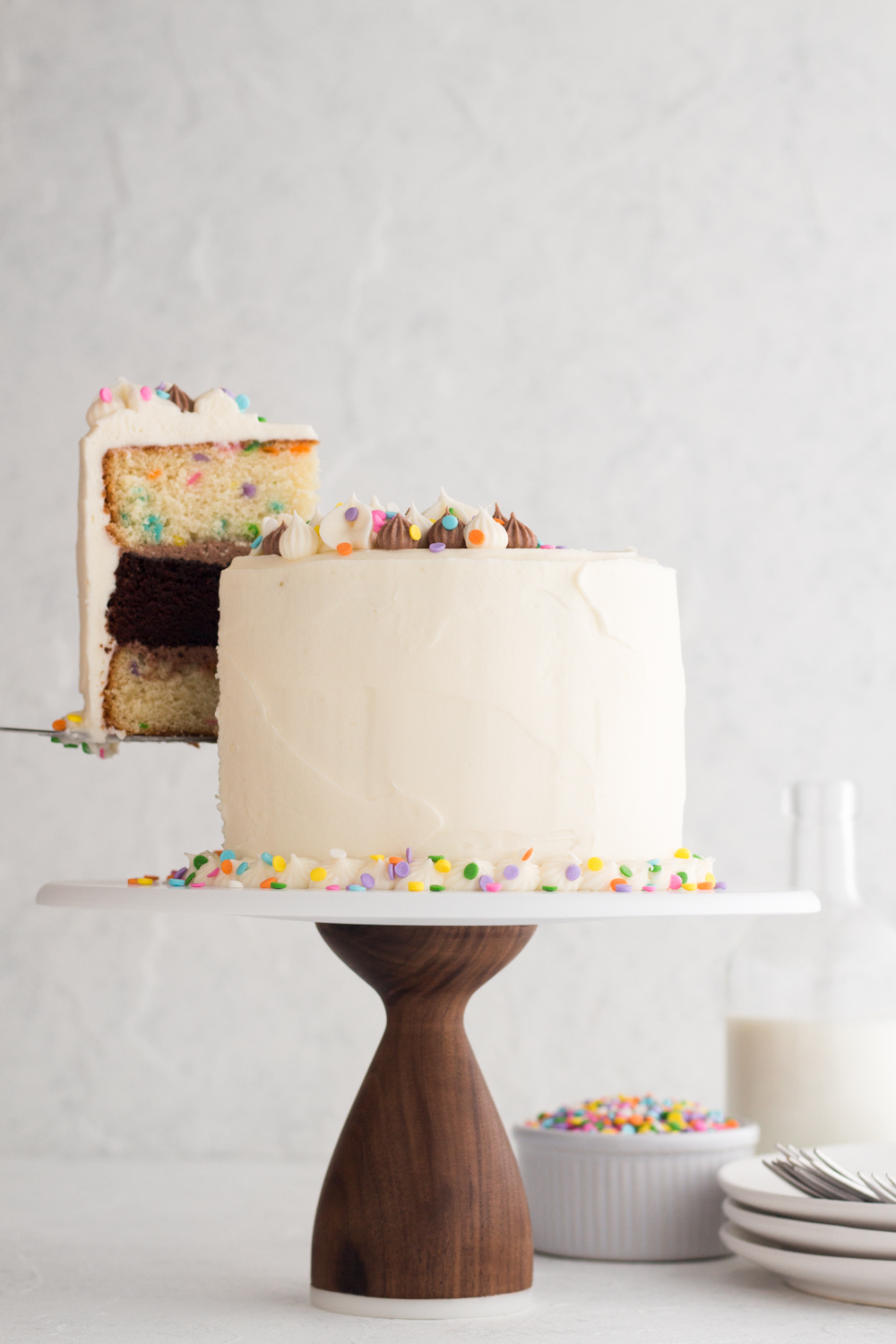 side view of funfetti layer cake with a slice being lifted up