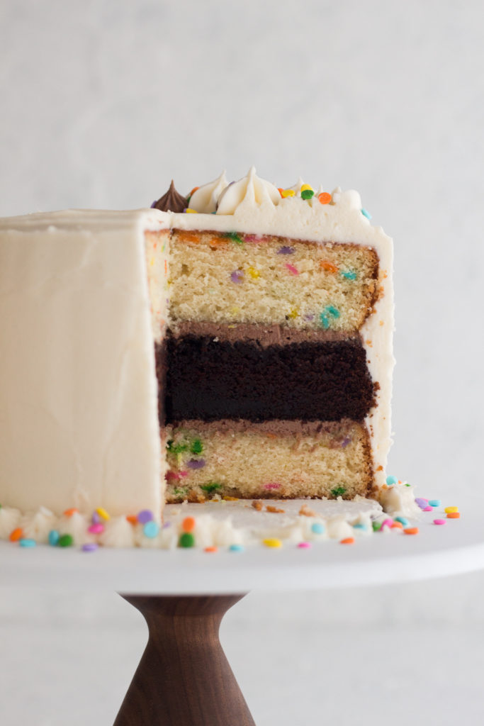 side view of funfetti layer cake with a large slice removed