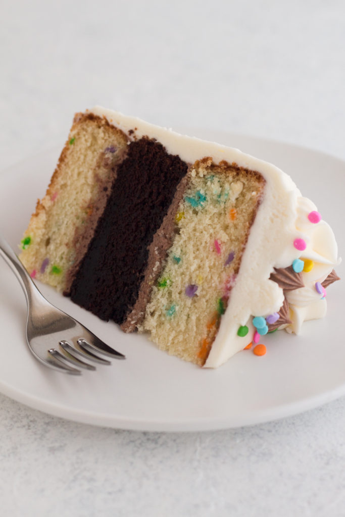 slice of funfetti layer cake on a white plate with a fork