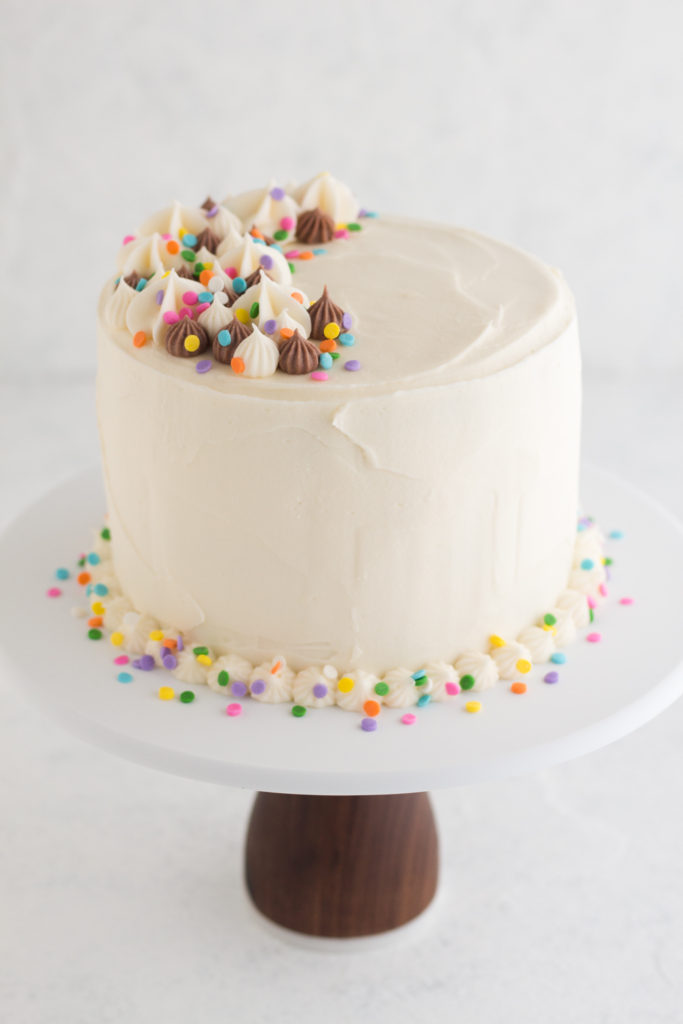 angled view of funfetti layer cake on a cake stand