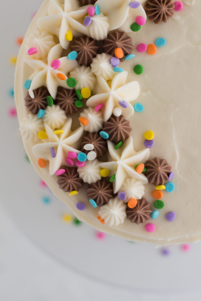 overhead view of funfetti layer cake with piped frosting and sprinkles