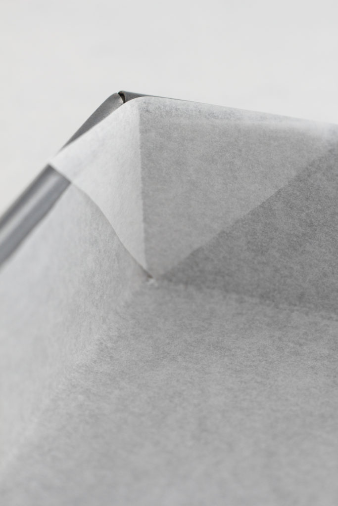 close up view of the corner of a square pan lined with parchment paper