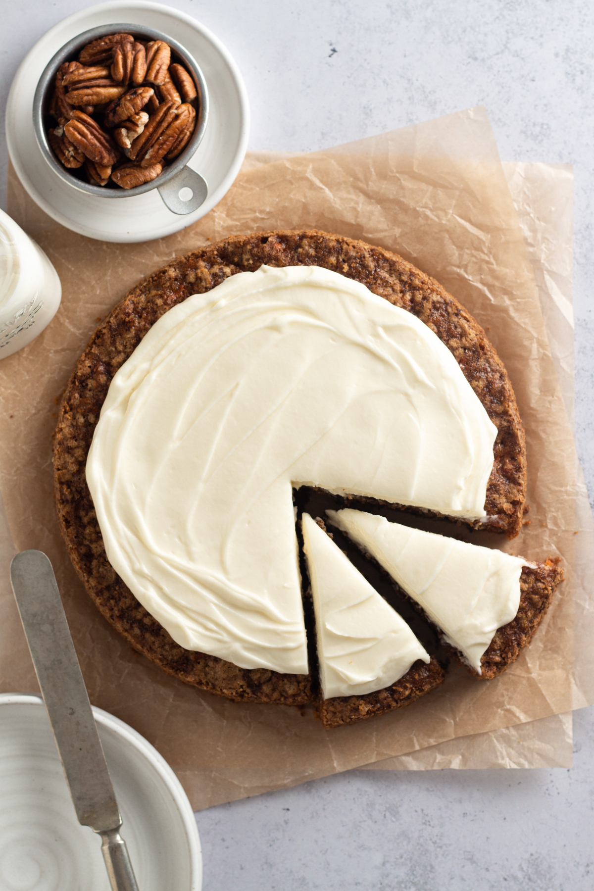 overhead view of a round carrot cake with cream cheese frosting with two cut slices